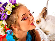 Woman in easter style kissing rabbit and flowers in basket. Easter girl holding bunny and eggs. Woman with holiday spring flowers hairstyle and make up kissing Royalty Free Stock Images