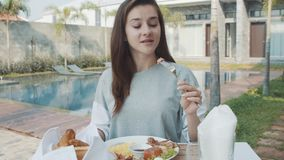 Woman eat breakfast with eggs, sausages, bacon, potato, tomato on luxury villa. stock footage