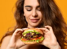Woman eat burger sandwich with hungry mouth on yellow background Royalty Free Stock Photos