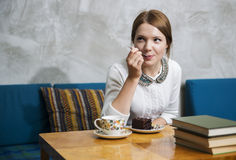 Woman eat cake with pleasure  at cafe Royalty Free Stock Photo