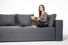 Woman eat chips on sofa and watch movie on laptop on white background Royalty Free Stock Images