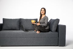 Woman eat chips on sofa and watch movie on laptop on white background Stock Images