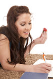 Woman eat strawberry homework writing. Stock Photos