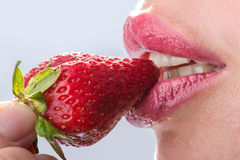 Woman eat strawberry. Seductive woman with red lips eating a fresh strawberry Stock Photos