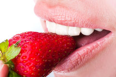 Woman eat strawberry. Seductive woman with red lips eating a fresh strawberry Stock Images