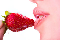 Woman eat strawberry. Seductive woman with red lips eating a fresh strawberry Stock Image