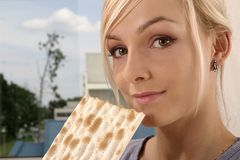 Woman eating. Blond, young girl, woman eating unleavened bread Stock Photography