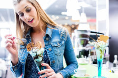 Woman eating amaretto sundae in ice cream cafe Stock Images