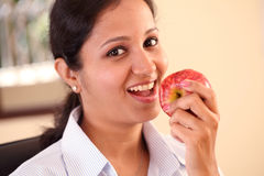 Woman eating apple. Young business woman eating an apple Stock Photography