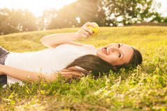 Woman eating apple. Stunning young brunette eating apple lying on grass in sunshine Royalty Free Stock Images