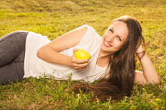 Woman eating apple. Stunning young brunette eating apple lying on grass in sunshine Stock Images