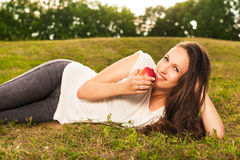 Woman eating apple. Stunning young brunette eating apple lying on grass in sunshine Stock Photo