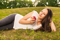 Woman eating apple. Stunning young brunette eating apple lying on grass in sunshine Stock Photos