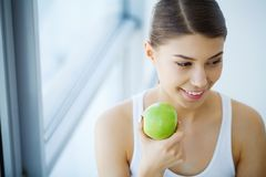Woman Eating Apple. Beautiful Girl With White Teeth Biting Apple. High Resolution Image royalty free stock photos
