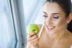 Woman Eating Apple. Beautiful Girl With White Teeth Biting Apple. High Resolution Image stock photo