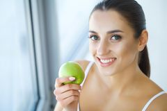 Woman Eating Apple. Beautiful Girl With White Teeth Biting Apple. High Resolution Image royalty free stock image
