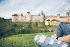 Woman eating an apple for breakfast outside in front of old castle Royalty Free Stock Photos