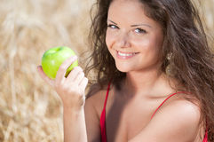 Woman eating apple in dield. Summer picnic. Royalty Free Stock Images