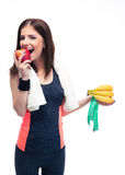 Woman eating apple and holding banana with measuring tape Royalty Free Stock Images