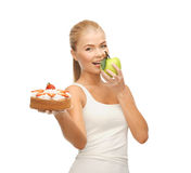 Woman eating apple and holding cake Royalty Free Stock Image