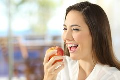 Woman eating an apple at home Stock Photos