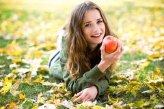 Woman eating apple outdoors in autumn