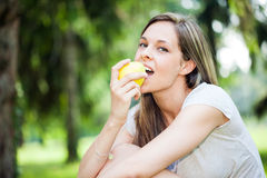 Woman eating an apple in the park Stock Images