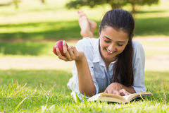 Woman eating apple while reading a book in park Stock Photos
