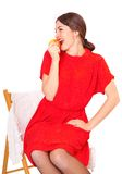 Woman eating an apple sitting on a chair Stock Photos