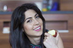 Woman eating apple smiling happy looking at camera. Healthy lifestyle - brunette  woman eating red apple Stock Photos