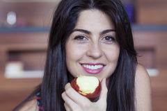 Woman eating apple smiling happy looking at camera. Stock Image