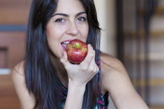 Woman eating apple smiling happy looking at camera. Stock Photo