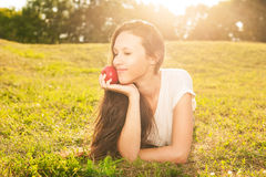 Woman eating apple. Stunning young brunette eating apple lying on grass in sunshine Stock Photography
