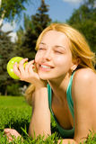 Woman eating apple on the summer glade Royalty Free Stock Photography