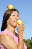 Woman eating an apple V Stock Photography