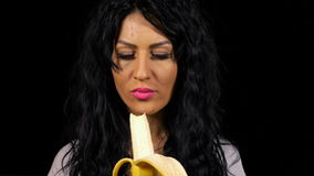 Woman eating a banana healthy lifestyle with black background. Young woman eating a banana healthy lifestyle with black background stock footage
