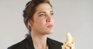 Close up of a woman eating a banana on a white studio background. Woman eating a banana on a white background stock video footage