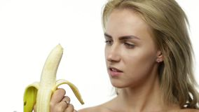 Woman Eating Banana. Young woman peeling and eating banana stock footage