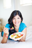 Woman eating on bed Royalty Free Stock Photography