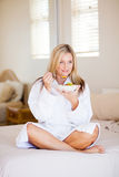 Woman eating on bed Stock Image