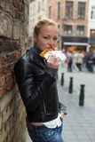 Woman eating belgian waffle on street of Brussels. Stock Photos