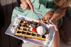 Woman eating belgium waffles with chocolate sauce. Closeup of woman eating belgium waffles with chocolate sauce, ice cream and strawberries in cafe Royalty Free Stock Image