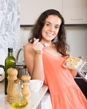 Woman eating biscuit in kitchen Stock Photo