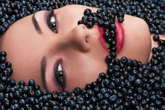 Woman is eating blueberries lying in blueberries Royalty Free Stock Photo
