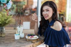 Woman eating blueberry cheese cake at cafe royalty free stock photography
