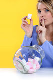 Woman eating bonbons Royalty Free Stock Image