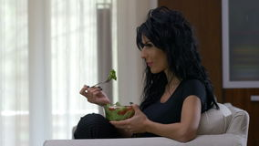 Woman eating a bowl of lettuce and tomatoes vegetable salad dish watching tv at home stock video