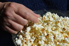 Woman eating a bowl of plain popcorn. Healthy snacks. Close-up a woman's hand and a bowl of air-popped plain popcorn, a healthy whole grain food made from a royalty free stock image