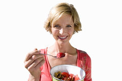 Woman eating a bowl of strawberries, cut out Royalty Free Stock Photo