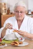 Woman eating breakfast. Senior woman eating her breakfast Royalty Free Stock Photos